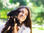 Young brunette woman hugging her lap dog puppy — Stock Photo