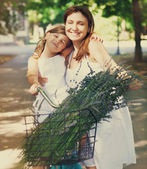 Beautiful and happy young woman on bicycle with her daughter — Stockfoto