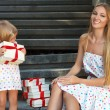 Cute little girl and her mother holding presents — Stock Photo