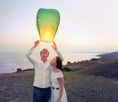 Young couple start a green Chinese sky lantern in the dusk — Stock Photo