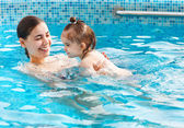 One year baby girl at her first swimming lesson with mother — Stock Photo