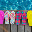 Brightly colored flip-flops on wooden background — Foto de Stock