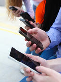Group of a students chatting with their smartphones — Stock Photo