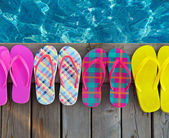 Brightly colored flip-flops on wooden background  — Stock Photo