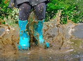 Child wearing blue rain boots jumping into a puddle — Stock Photo