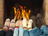 Feet warming near the fireplace — Stock Photo