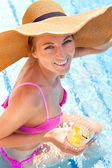 Woman in a hat enjoying cocktail in a swimming pool — Stock Photo