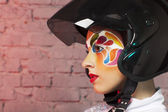 Beautiful young model with bright creative make up with helmet — Stock Photo