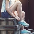 Blue sneakers on girl legs on the grunge background — Stock Photo #49599869