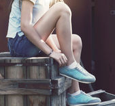 Blue sneakers on girl legs on the grunge background — Stock Photo