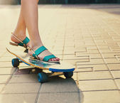 Teen girl on longboard on the street  — Stock Photo