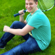 Teenage boy smiling while holding a tennis racket  — Stock Photo #49789025