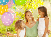 Happy woman and her little daughters in the park with ballons — Stock Photo