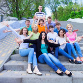 Group of smiling teenagers sitting on the stairs  — Stock Photo