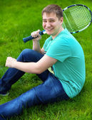 Teenage boy smiling while holding a tennis racket  — Stock Photo