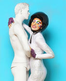Model with bright creative make up with helmet and male dummy — Stock Photo