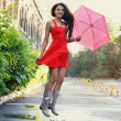 Portrait of beautiful young girl with umbrella under rain — Stock Photo #50264345