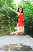 Young happy woman wearing red dress jumping into a puddle — Stock Photo