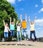 Group of smiling teenagers jumping outdoors — Stock Photo