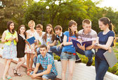 Group of students or teenagers with notebooks outdoors — Stock Photo