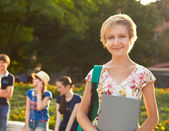 Female smiling student outdoors in the evening with friends — Stock Photo