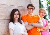 Groupe d'adolescents souriants, assis à l'extérieur — Photo