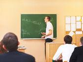 Vista posteriore di studenti ad ascoltare attentamente studente maschio — Foto Stock