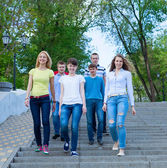 Group of smiling teenagers walking outdoors — Stock Photo