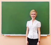 Student girl standing near blackboard in the classroom — Stock Photo