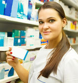 Pharmacist showing medicine box at pharmacy counter — Stock Photo