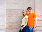 Couple standing near the wall outdoors — Stock Photo