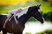 Child sits on a horse — Стоковое фото
