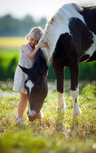Child stands with a horse — Stock Photo