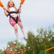 Happy girl jumping in amusement park - Stok fotoğraf