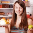 Young woman with apple and cake on background fridge — Stock Photo