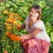 Smiling women with flowers outdoor — Stock Photo