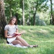 Beautiful girl with book outdoor - Zdjęcie stockowe