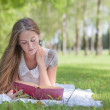 Beautiful girl with book outdoor - Stockfoto