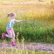 Girl jumping over a skipping rope — Stock Photo #18612327
