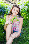 Beautiful girl with flowers in garden — Stock Photo