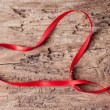 Tape in the form of heart on wooden background — Stock Photo