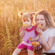 Mother and little girl with peach outdoor — Stock Photo