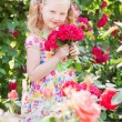 Happy girl with roses in garden - Stock Photo