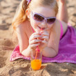 Little girl drinks orange juice outdoor — Stock Photo