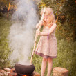 Little witch making potions outdoor - Stock Photo