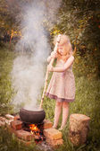 Little witch making potions outdoor — Stock Photo