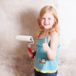 Smile girl painting the wall - Stock Photo