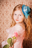 Little girl with rose on background wallpaper — Stock Photo