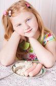 米のポリッジとソーセージのボールを持つ少女 — ストック写真