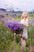 Girl with flowers in the field — Stock Photo